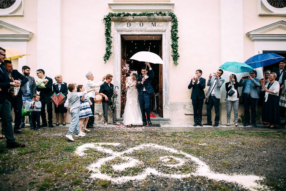 sposi escono dalla chiesa con ombrello bianco