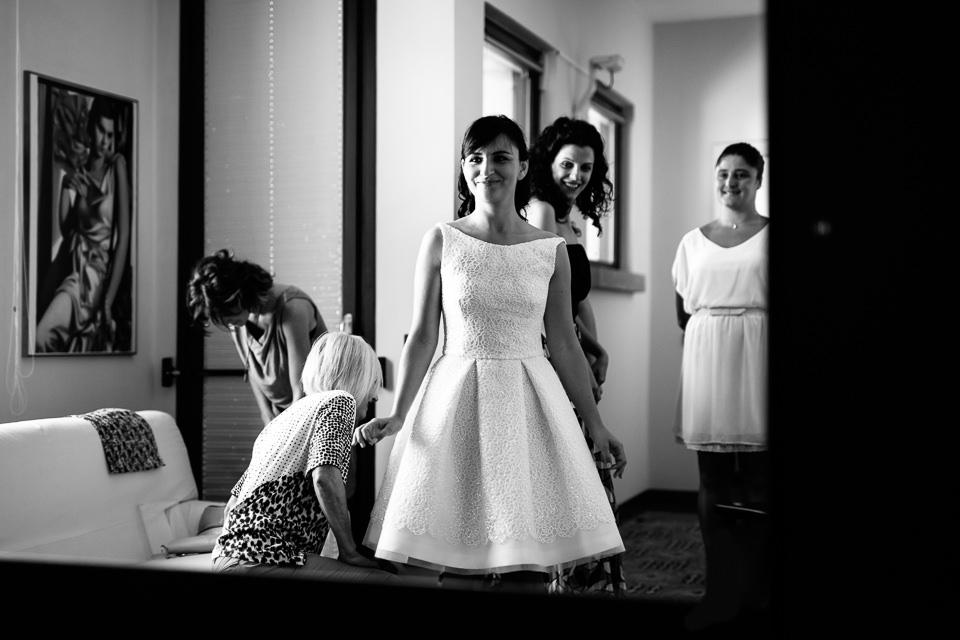 sposa sorridente si specchia con il suo abito da sposa