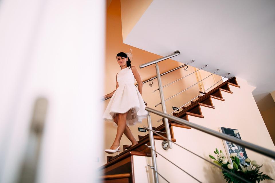 sposa in abito bianco e corto scende le scale di casa
