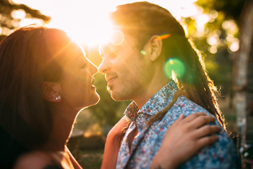 boy with dreadlocks kisses tattooed girl at sunset