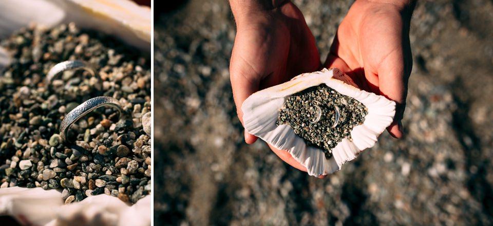 fedi nuziali in oro bianco artigianali poste all'interno di una conchiglia piena di sabbia del mare