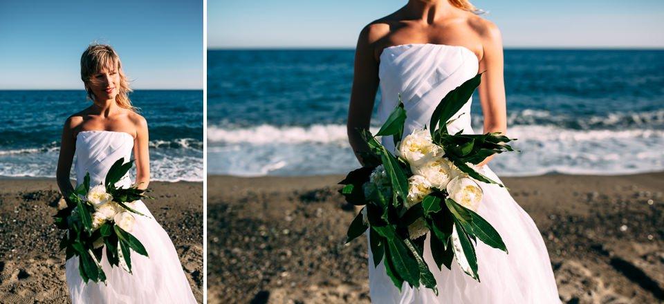 sposa in riva al mare con in mano il suo bouquet di rose bianche