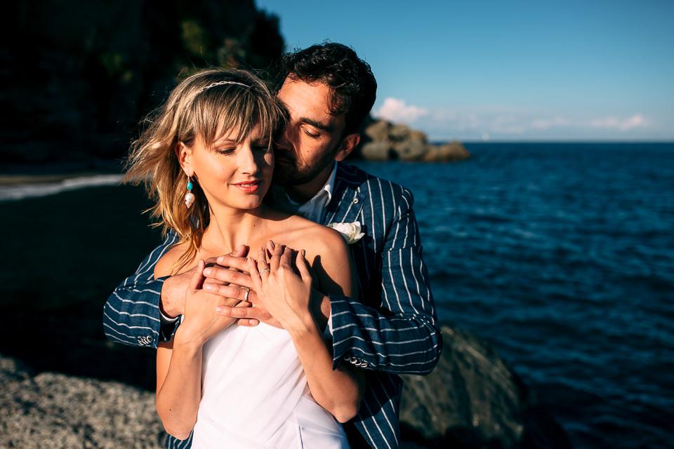 coppia di sposi abbracciati in riva al mare