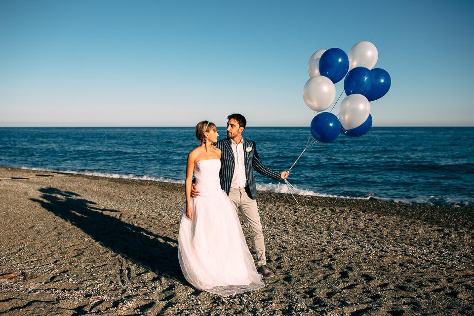 coppia di sposi al mare con palloncini bianchi e blu