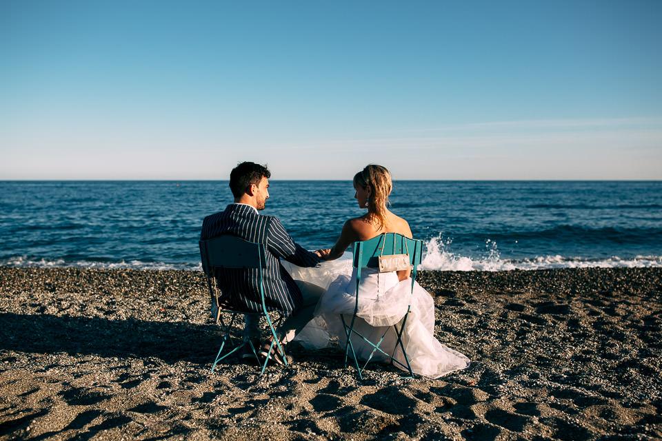 coppia di sposi seduti su due sedie vintage al mare
