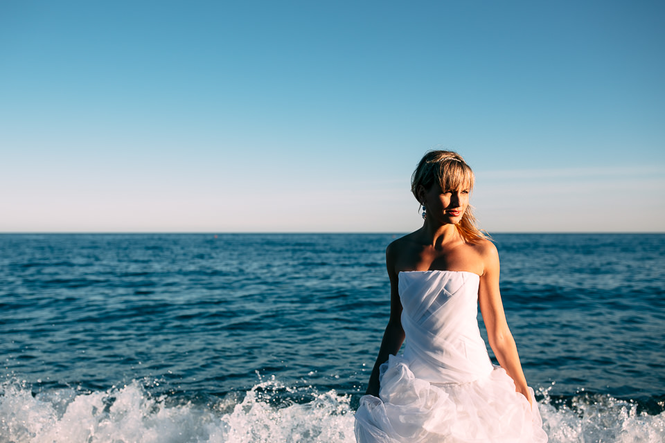 bride in white dress walks on the wet sand of the sea