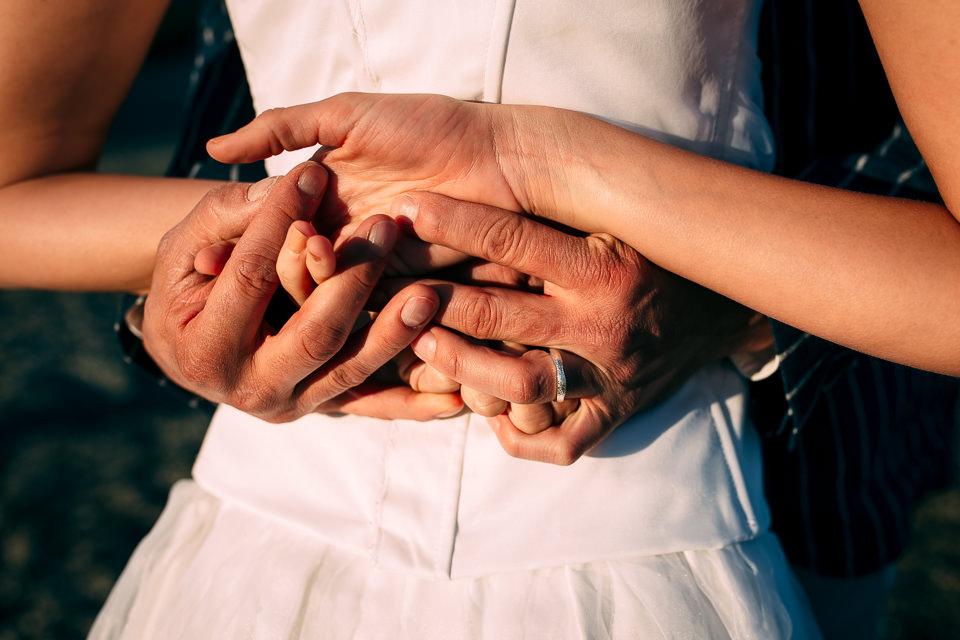 mani intrecciate di una coppia di sposi per un matrimonio al mare