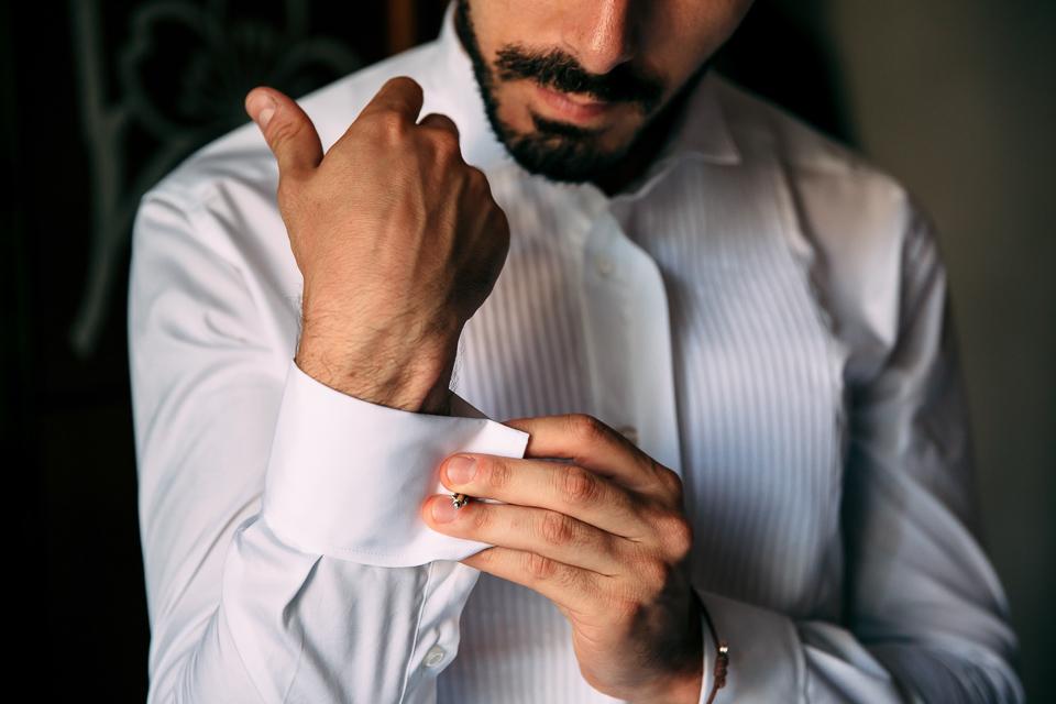preparativi dello sposo in camicia bianca