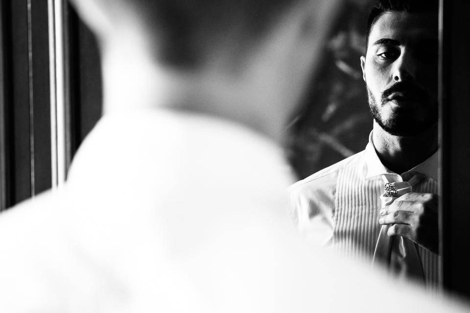 lo sposo si specchia per fare il nodo alla cravatta