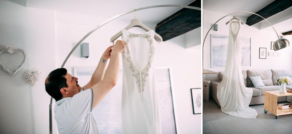 il padre della sposa appende l'abito bianco del matrimonio al lampadario