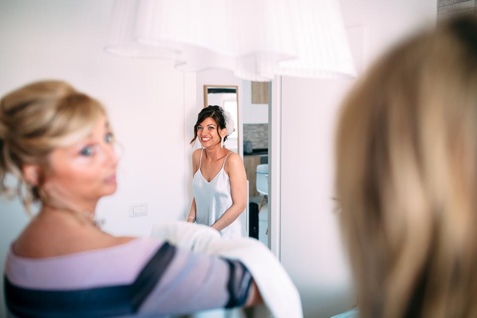 la sposa si appresta emozionata a vestire il suo abito bianco da sposa