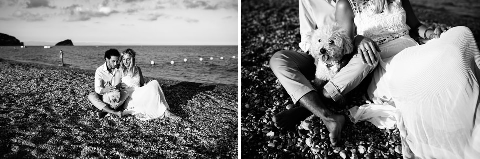 coppia di innamorati vestiti di bianco sono seduti sulla sabbia con il loro barboncino bianco