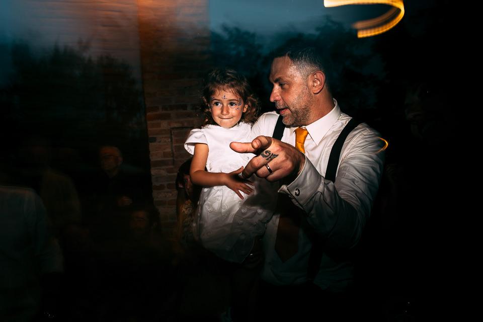 lo sposo in bretelle con la figlia in braccio