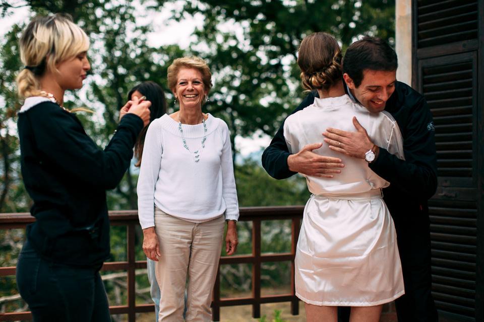 fratello abbraccia la sposa in vestaglia bianca
