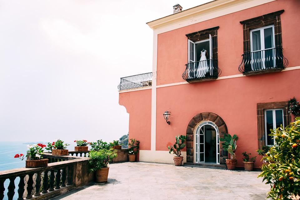 abito da sposa bianco dell'atelier le spose di milano appeso alla finestra della suite di vill magia a Positano