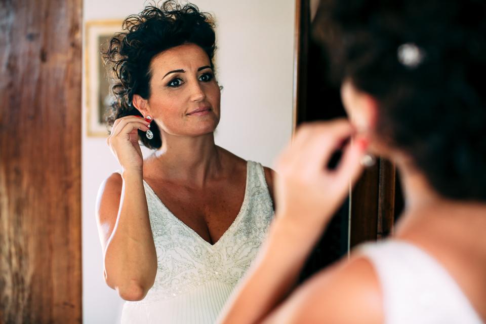 sposa in abito bianco mette gli orecchini
