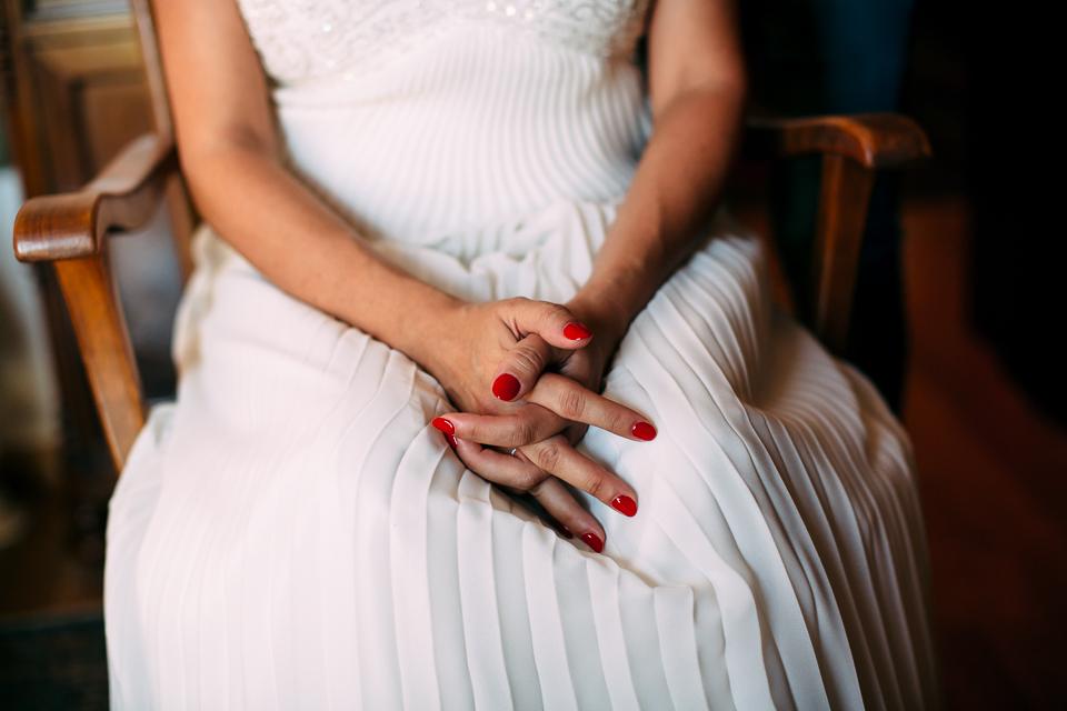 abito bianco da sposa e smalto per le unghie rosso
