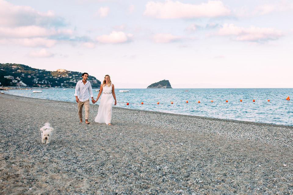 giovani fidanzati passeggiano al mare con il loro barboncino bianco