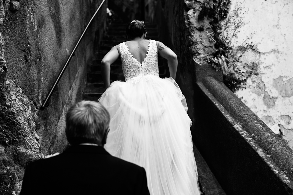 elegant bride in a white dress climbs the positano steps to get married