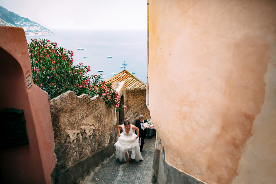 elegant bride in white dress goes up the steps of Positano, Amalfi Coast