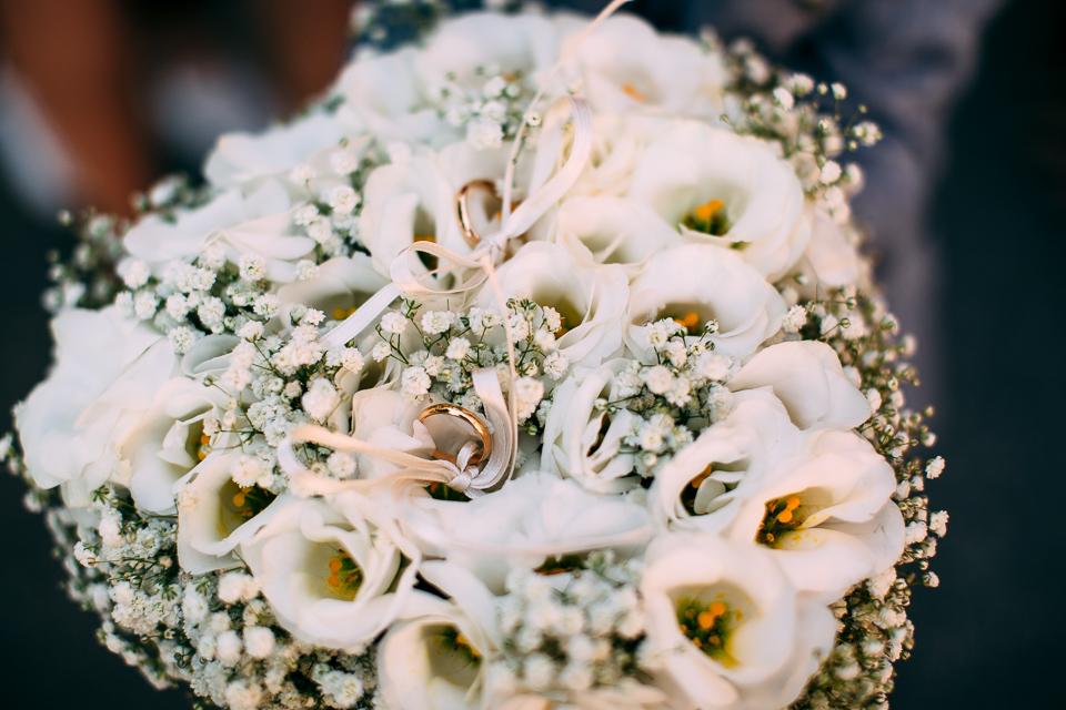 fedi nuziali in oro giallo su rose bianche, matrimonio in toscana