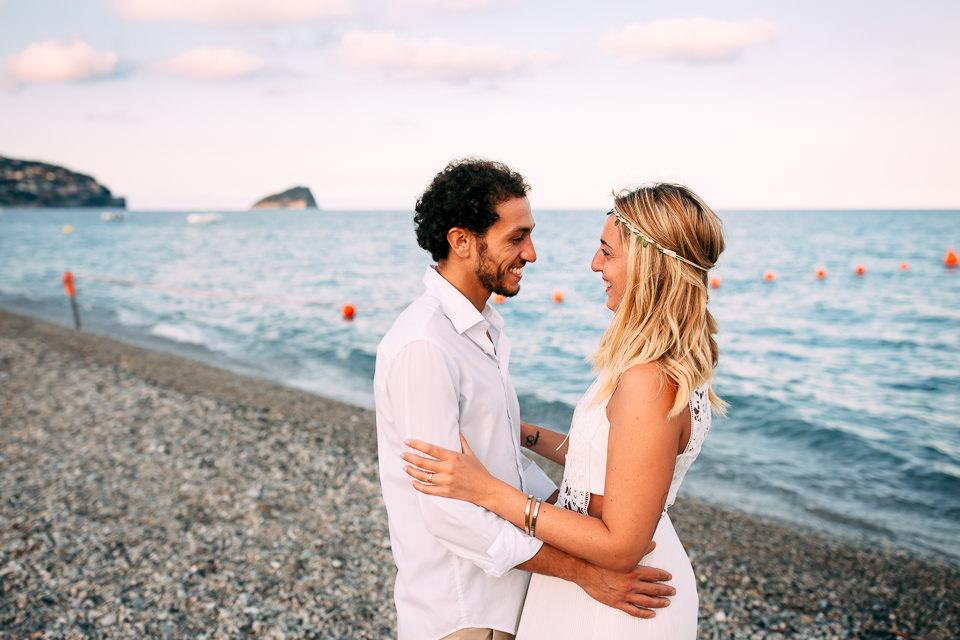 coppia di fidanzati vestiti di bianco si abbracciano in spiaggia