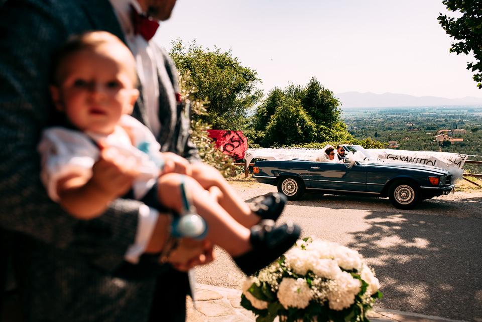 arrivo della sposa in chiesa su automobile sportiva con dietro le colline toscane