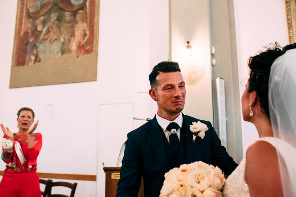 sposo che piange abbraccia la sposa in abito bianco
