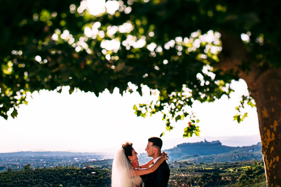 sposi si abbracciano su un bellissimo panorama in toscana