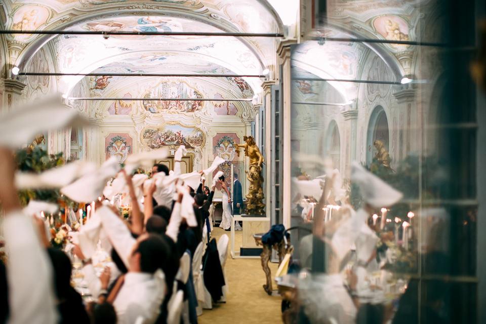 ingresso degli sposi nella bellissima sala apparecchiata con una tavolata imperiale, gli invitati sventolano i tovaglioli