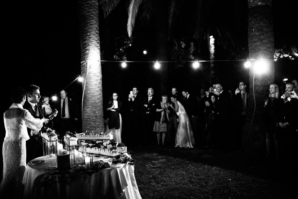 taglio della torta di un matrimonio serale all'aperto