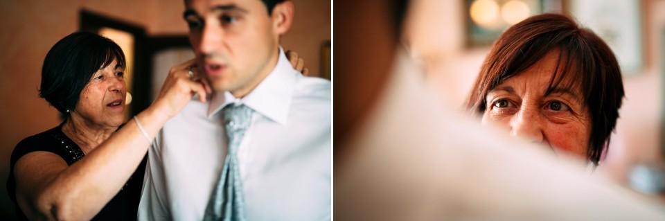 la mamma dello sposo aiuta il figlio a vestirsi
