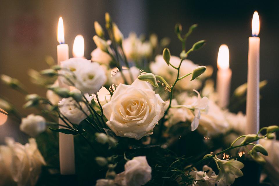 dettaglio floreale di una rosa bianca e delle candele in chiesa