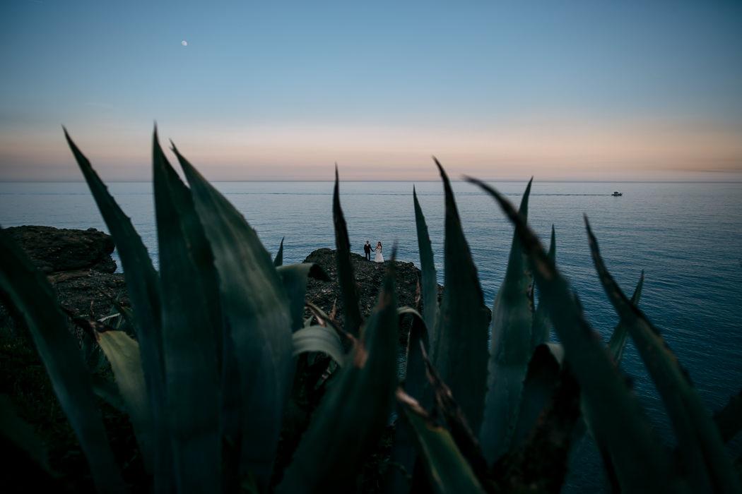 coppia di sposi al tramonto sugli scogli