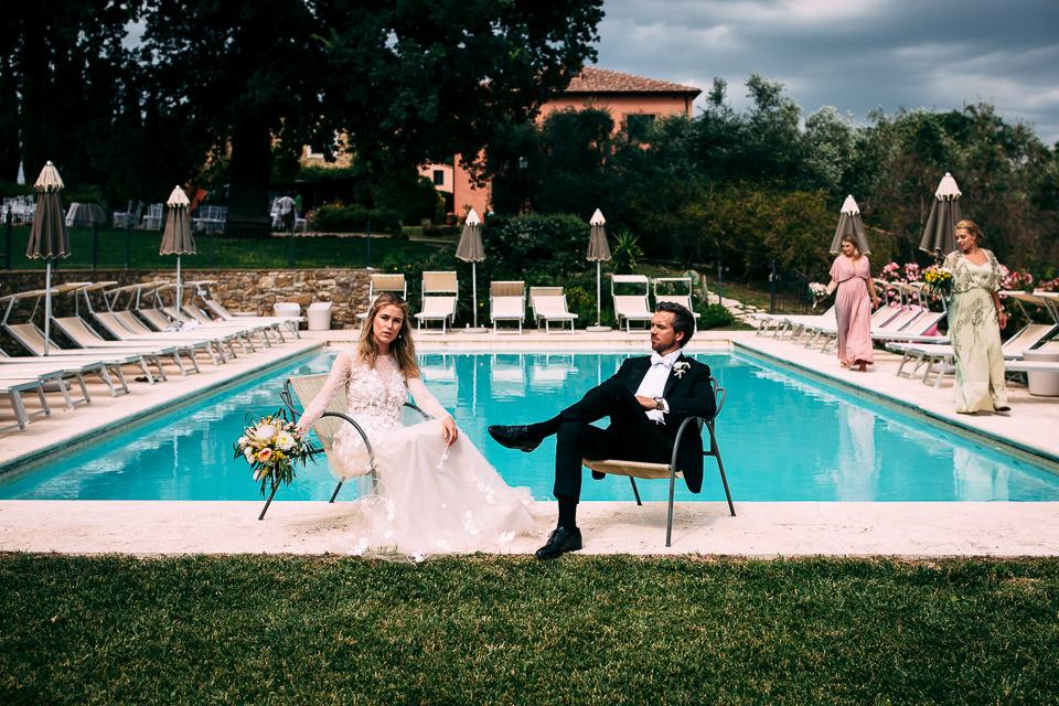 elegante ritratto di una coppia di sposi a bordo piscina in toscana