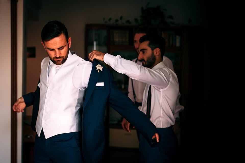 sposo indossa la sua giacca blu